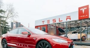 Electric car parked in front of Tesla dealership; image courtesy of www.dailyreckoning.com.au.
