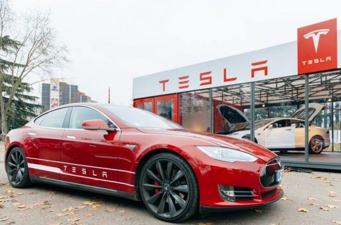 Electric car parked in front of Tesla dealership; image courtesy of www.dailyreckoning.com.au.
