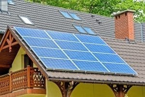 Rooftop solar panels adorn a house with intricate wooden trim.