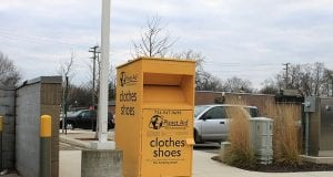 A Planet Aid clothing donation box sits on a curb in a parking lot.