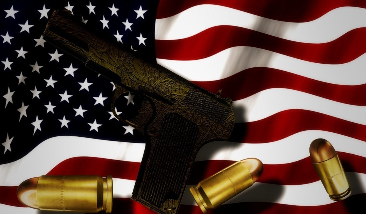 Gun and bullets atop an American Flag; image by kalhh, via Pixabay.com, CC0.