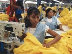 A woman with dark skin sews clothing in a sweatshop factory, surrounded by identically dressed women also sewing clothes.