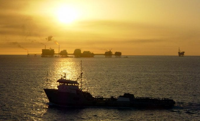 A ship and oil rigs in the Gulf of Mexico, at twilight.