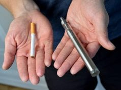 Two hands offer a choice of a traditional cigarette or an electronic cigarette.