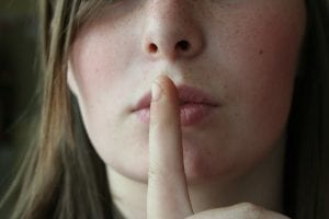 Woman holding finger to lips to show silence; image by philm1310, via Pixabay.com CC0.