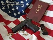 A gun, several bullets, and a Holy Bible lie strewn atop a wrinkled American flag.