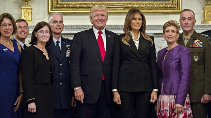 Donald and Melania Trump, surrounded by military men and others, pose for a photo op.