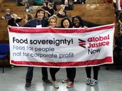 A diverse array of attendees at a 2015 UK food sovereignty gathering hold a banner. It says Food sovereignty! Food for People, not for corporate profit / Global Justice Now.