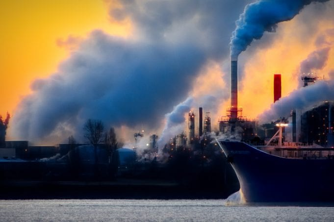 Thick blue smoke rising from an industrial complex in front of a glowing sky.