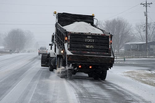 A salt truck seasons a snow-covered road to prevent ice buildup and keep drivers safe.