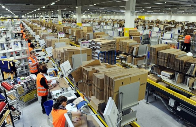 Amazon workers at a conveyor belt in a cavernous warehouse, shelves of goods as far as the eye can see.