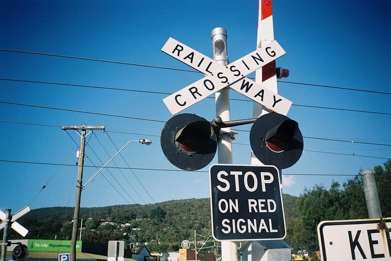 """A railroad crossing. The sign says """"Railroad Crossing"""" and """"Stop on Red Signal."""""""