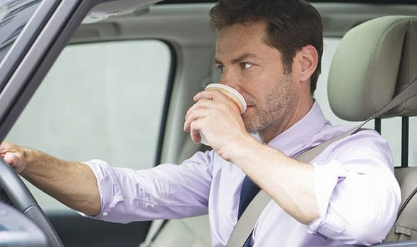 Man drinking coffee while driving; image courtesy of www.express.co.uk.