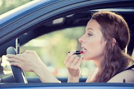 Woman applying lipstick in car; image courtesy of www.valleyparentmagazine.com.