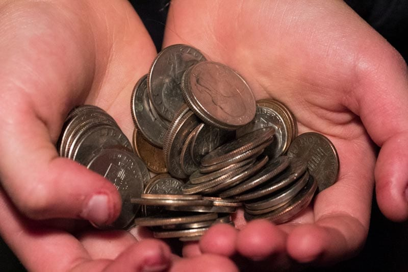 Caucasian hands cupped together, holding a collection of small change.