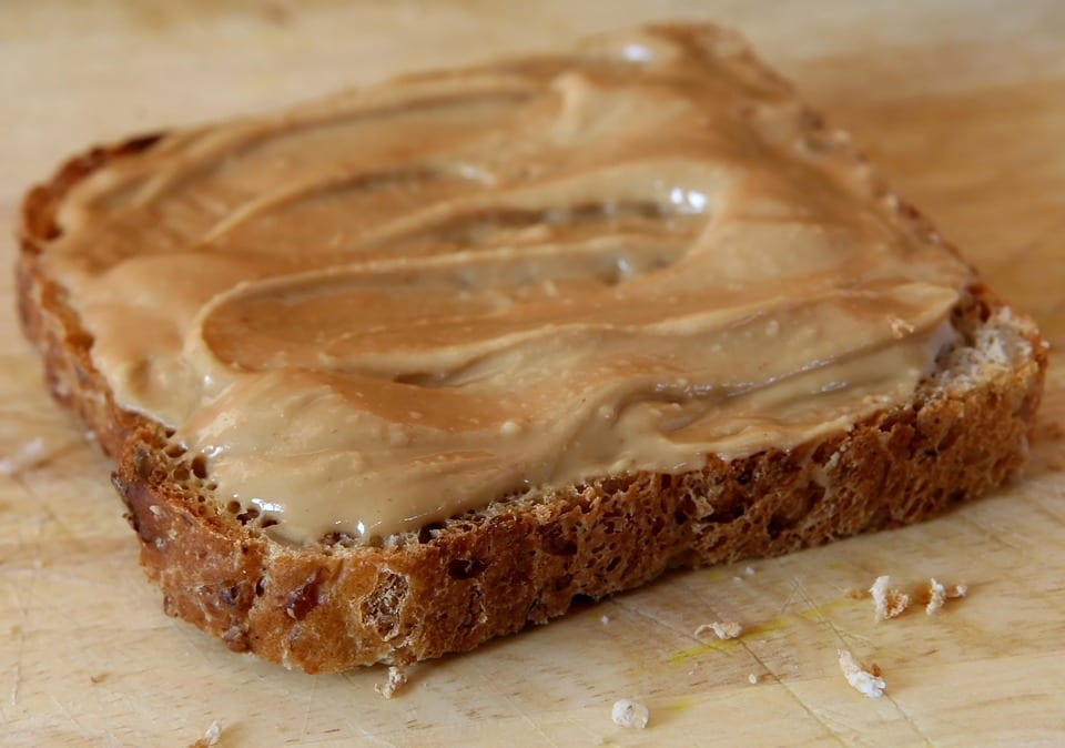 A slice of wheat bread with a thick spread of peanut butter, sitting on a wooden surface.