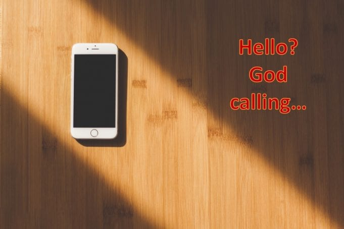 """Cellephone on table, text saying """"Hello? God calling...""""; image via Negative Space on www.pexels.com by CC0; text added by author."""