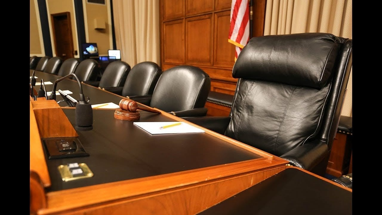 Empty chairs in a House of Representatives hearing room.