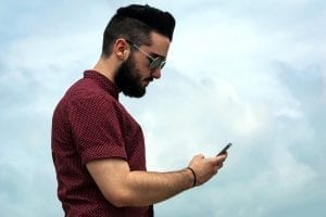 Man with beard checking smartphone; image courtesy www.pxhere.com, Creative Commons CC0.