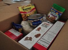 A box of donated, shelf stable foods like ramen, canned chicken, cookies, rice, and peanut butter, similar to what the harvest box might contain.