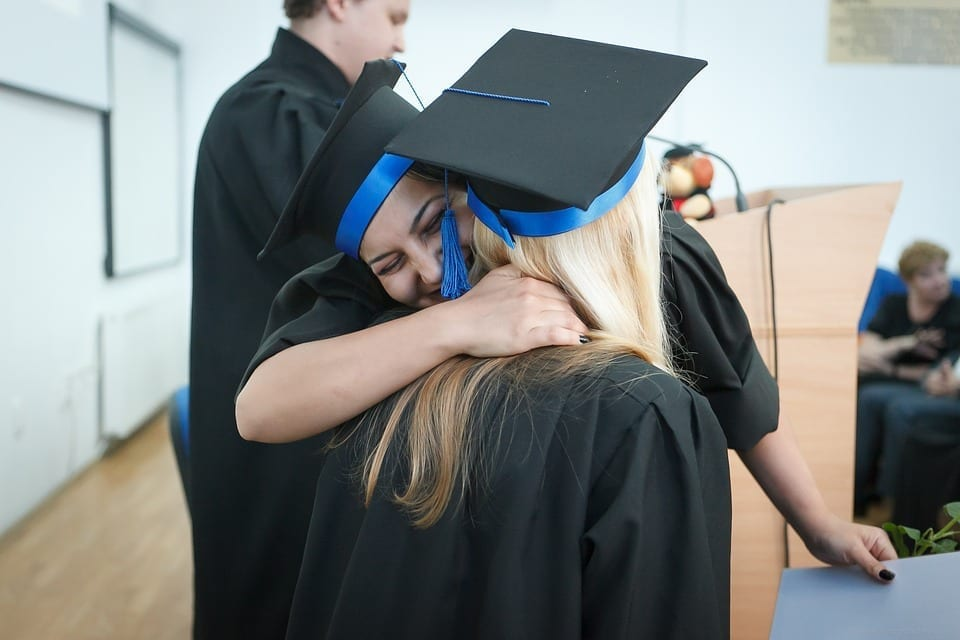Image of two college grads embracing