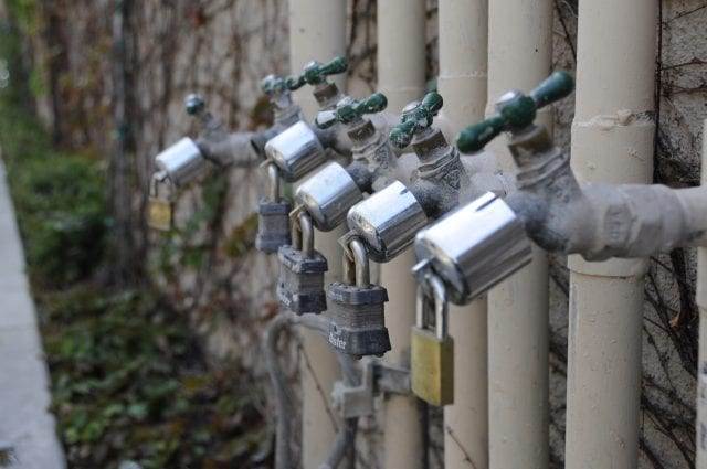 Water shortage, padlocked faucets; image courtesy Andrew Hart via Flickr.com, CC BY-SA 2.0, no changes.
