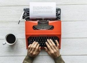 Writer typing on a typewriter
