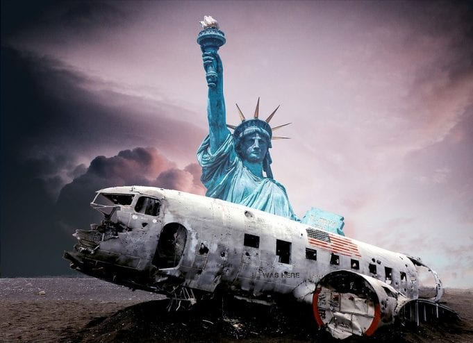 The ruined remains of a crashed airplane lay broken in front of the Statue of Liberty, backed by an ominously cloudy sky.