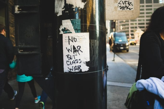 """A handwritten sign on ripped paper attached to a pole in Chicago reads """"No War But Class War."""""""