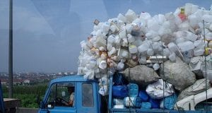 A blue pickup truck piled high with empty plastic jugs driven along a Chinese highway by a modern-day rag and bone man.