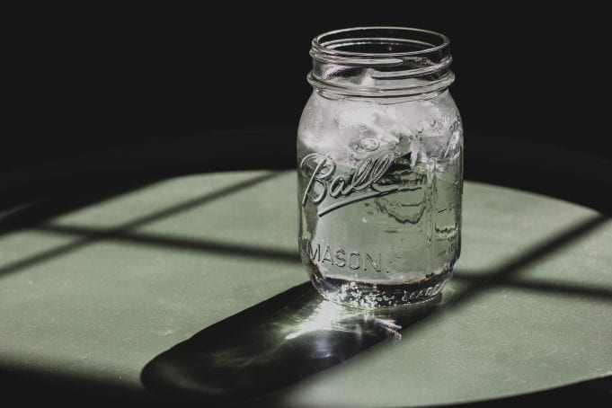 Sunlight filters through a Ball jar of clear, icy water sitting on a grey surface with a dark background.