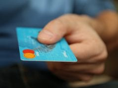 Customer presenting credit card; image courtesy of Pxhere.com, CC0.