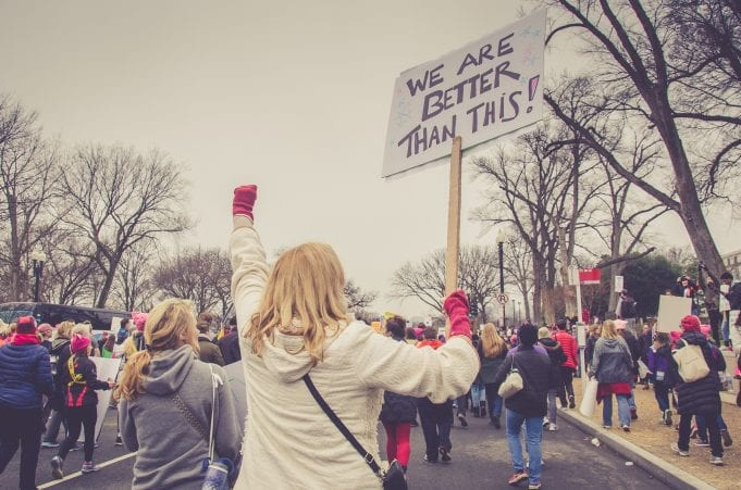 """A blond woman, viewed from behind, holds up a fist and a protest sign that reads, """"We are better than this!"""""""