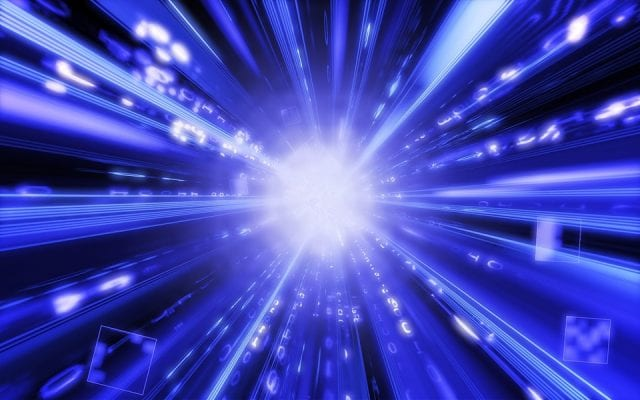A shining burst of white light at center, surrounded by rays of blue and white light radiating outwards from the center, backed by a dark void.
