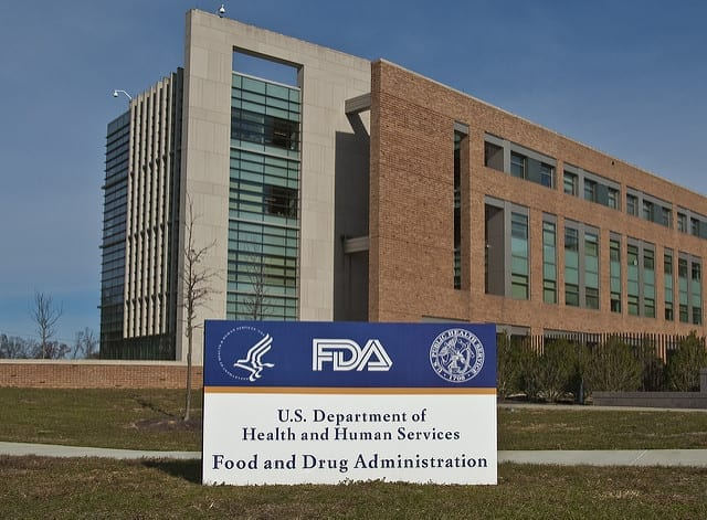 FDA Building 21 stands behind the sign at the campus's main entrance and houses the Center for Drug Evaluation and Research; image by FDA, Public domain.