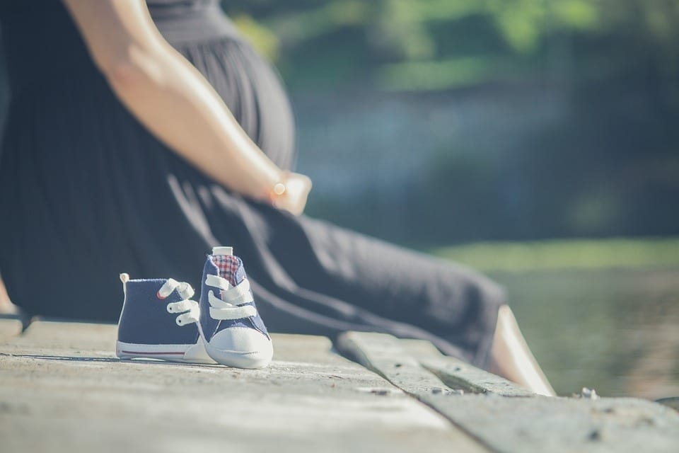 Image of a Pregnant Woman and Baby Shoes