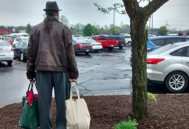 A long-haired man in a leather jacket, toting cloth bags full of groceries, faces away from the observer as he scans a parking lot.