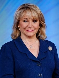 Governor Mary Fallin portrait. She's wearing a dark blue top with a gemstone cross necklace.