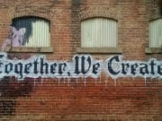 "The words ""Together, We Create!"" are skillfully painted on a brick wall below a row of windows."