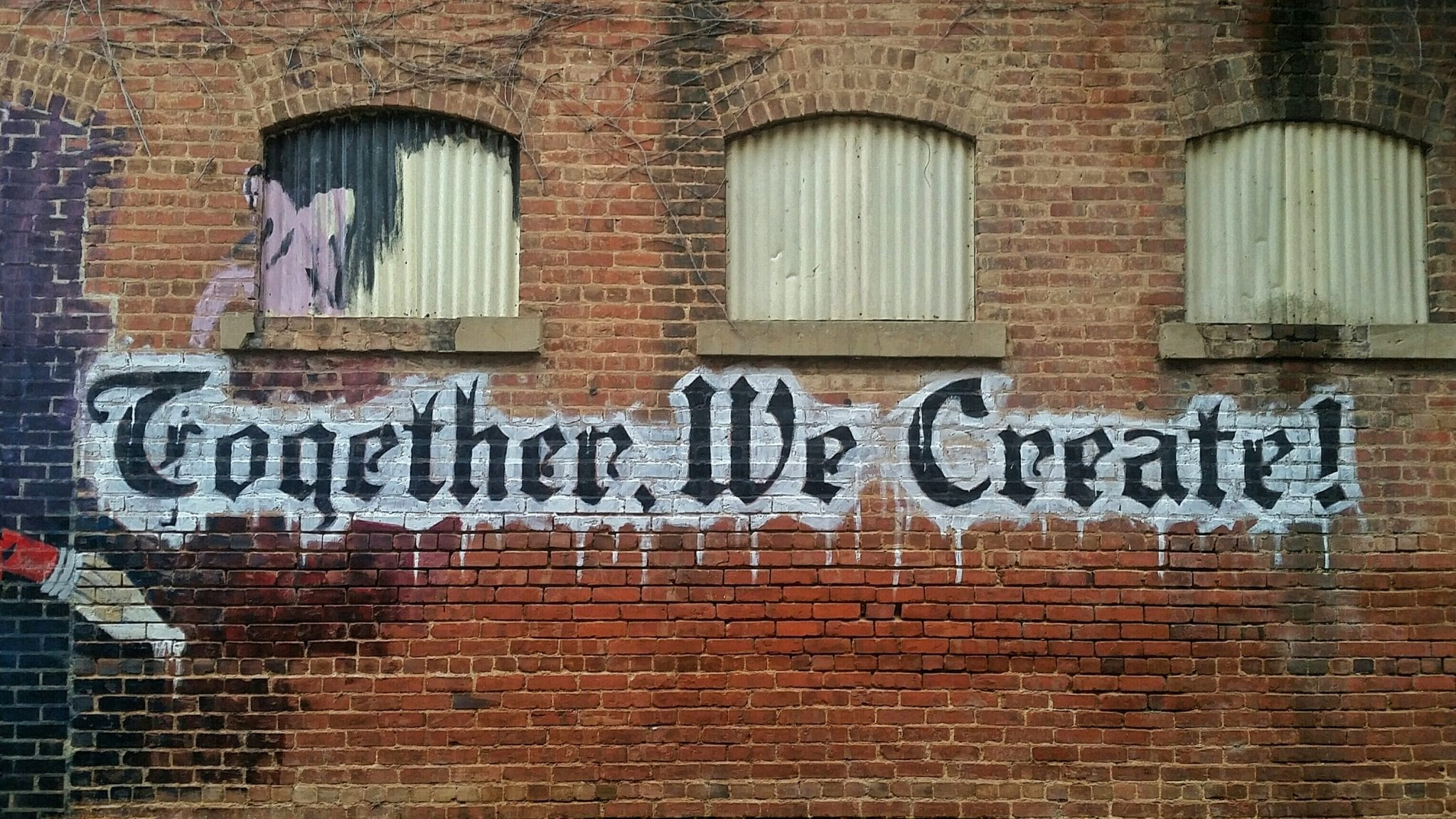 """The words """"Together, We Create!"""" are skillfully painted on a brick wall below a row of windows."""