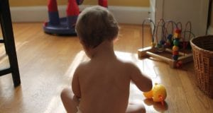 A caucasian baby, seen from behind, playing on a wooden floor with a few toys in the background.