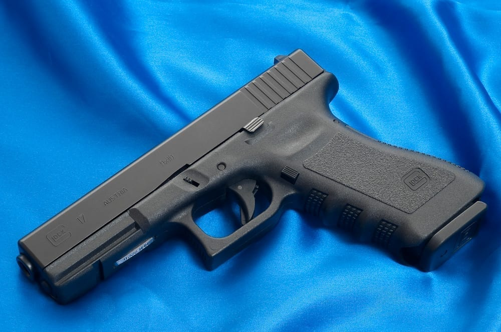 """An early """"third generation"""" Glock 17 (full-size pistol chambered for 9x19mm Parabellum), identified by the addition of thumb rests, an accessory rail, finger grooves on the front strap of the pistol grip and a single cross pin above the trigger. Image courtesy of Ken Lunde (own work), http://lundestudio.com, CC BY-SA 3.0, via Wikimedia Commons, no changes."""