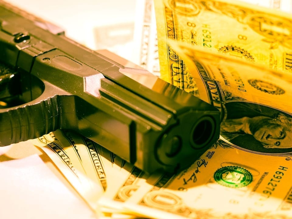 Image of a pistol and dollar bills