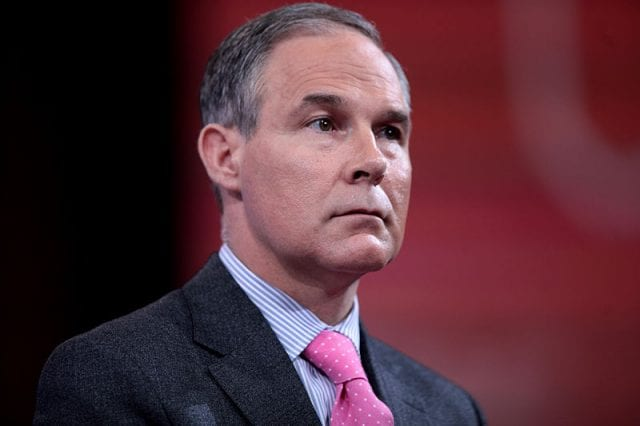 A portrait of an unsmiling Scott Pruitt, wearing a grey suit with a red tie, against a somewhat blurry red and black background.