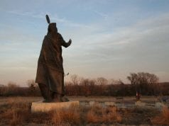 A larger than life statue of a Native American chief, from behind, at twilight.