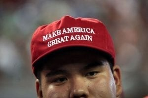 "A man wearing a red hat that says ""Make America Great Again."""