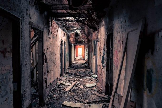 A decrepit, falling-apart hallways leads to an uncertain light.