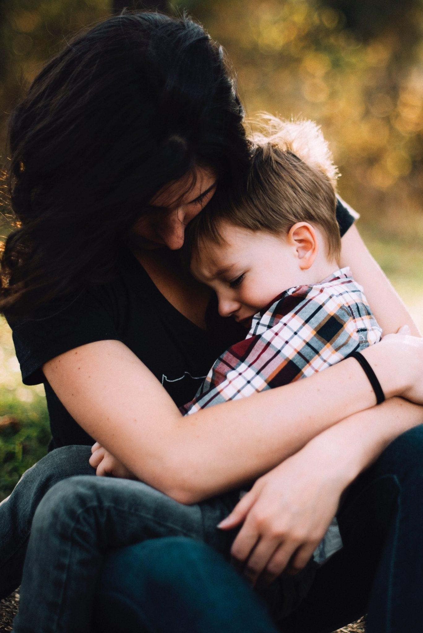 Woman hugging upset little boy; image by Jordan Whitt, via Unsplash.com.