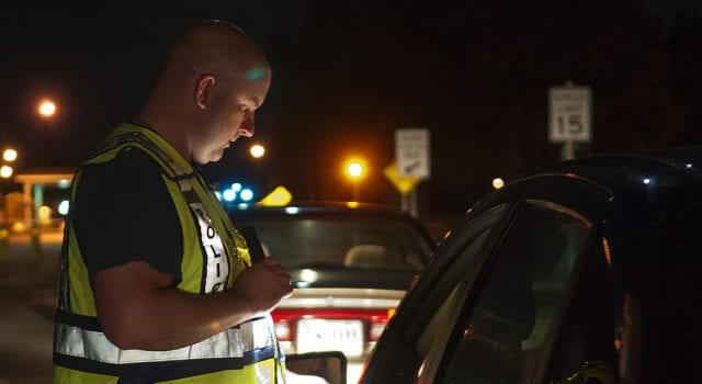 A police officer with a flashlight peers into the driver's side window of a car at night.