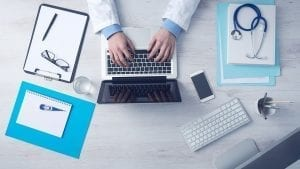 Image of a doctor working at a laptop